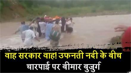 वाह सरकार वाह! उफनती नदी के बीच चारपाई पर बीमार बुजुर्ग