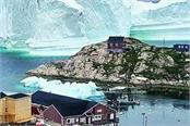 massive iceberg looms over a village in greenland