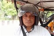 the driver driving an e rickshaw with the help of helmet fearing