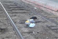 a little girl searching food on railway track