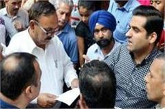 debate with administration encroachment  shopkeeper sitting in front on jcb