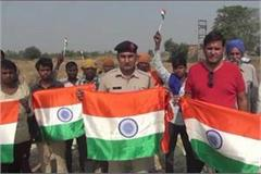 police man distributing a tricolor to prevent burning parali