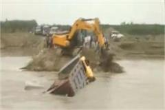 broken bridge on yamuna river and dumper flowing into water