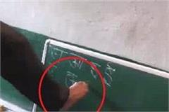 haridutt writes on the black board with legs