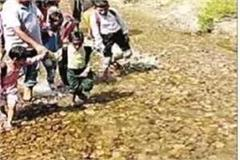 parents make children cross the ravine by holding hands