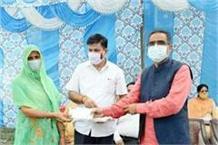 industry minister distribute cheque to eligible families