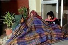 mother sitting with 2 children on dharna in the bitter cold
