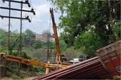 truck filled with electric poles overturned lifted crane also overturned