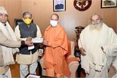 cm yogi meets vhp for ram temple construction handed over 2 lakh