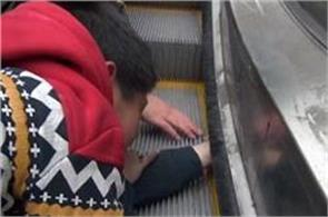 six year old boy gets his hand stuck in the rolling belt of an escalator