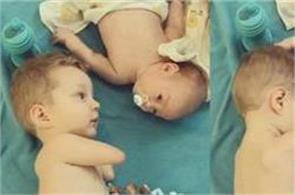 without hands baby gives pacifier to baby brother