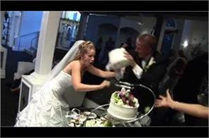 groom smashes cake on bride face