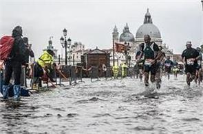 marathon runners splash through flooded street