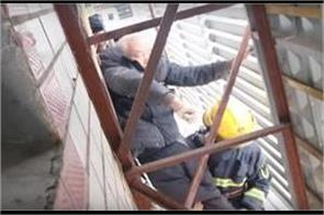 man falls from balcony  gets stuck on adve rtising board