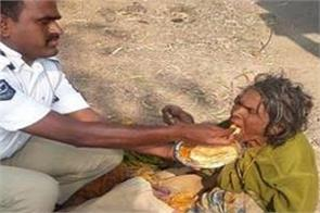 the policeman feeding a poor woman