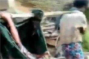 a pregnant woman being carried by her relatives
