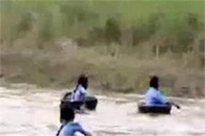 students cross the river using aluminium pots to reach their school