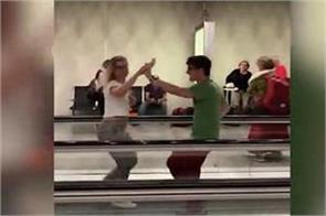 couple do salsa on airport walkway