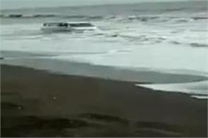 video car gets nearly swept into sea at maharashtra beach