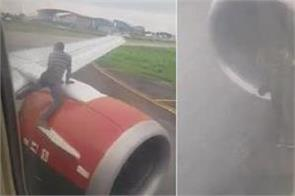 man climbs on to wing of plane as it is about to take off