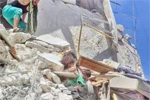 syrian girl grabs baby sister from shirt in a bombed building
