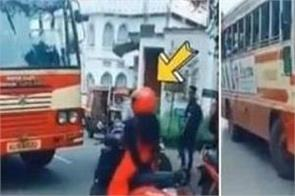 the woman parked scooty in front of the bus running on the wrong side