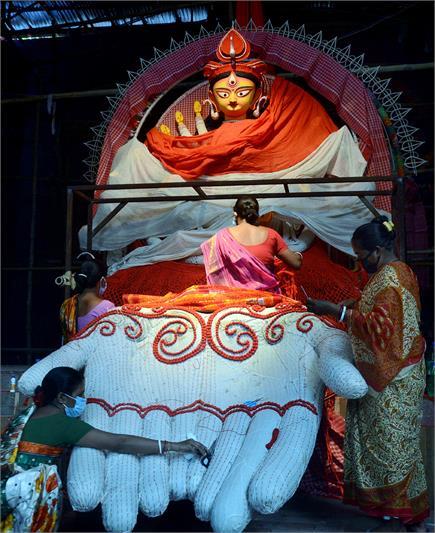 दुर्गा पूजा उत्सव से पहले देवी दुर्गा की मूर्तियों को तैयार करते...