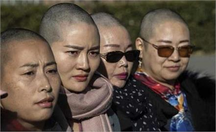 wife of detained china activist goes bald for justice