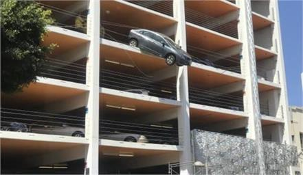 woman driver hit accelerator car hangs from 4th floor parking in air