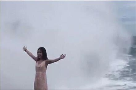 huge wave sweeps away woman posing on cliff