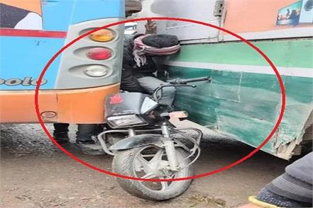 youth with bike stuck between 2 buses