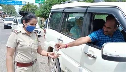 women police put a rakhi on wrist of mask and helmet