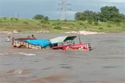 tractor full of school books got stuck in the strong current of the river
