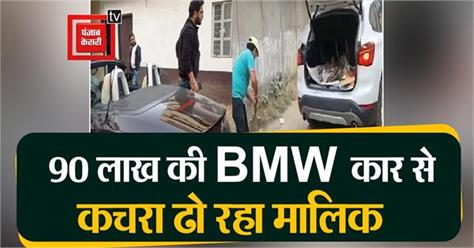 a young man carrying garbage in a bmw car